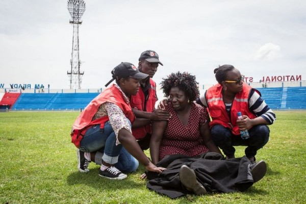 Dans le stade de Nyayo, à Nairobi, au Kenya, des membres de la Croix Rouge aident une femme dont un proche a été tué par les shebab somaliens lors de l'attaque de l'université de Garissa. (Photo Nichole Sobecki. AFP) (http://www.liberation.fr/monde/2015/04/07/tuerie-de-garissa-deux-poids-deux-mesures_1236147)